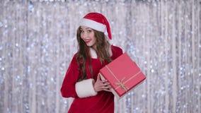 Santa kobiety chwyty prezent w ona ręki i przedstawienia aprobaty tła bokeh muzyczne notatki tematowe zbiory