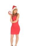 Santa kvinna i en röd klänning med en julgåva Royaltyfri Foto