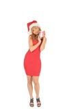 Santa kvinna i en röd klänning med en julgåva Arkivbilder