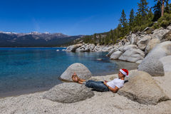Santa in Lake Tahoe. Adult male wearing a santa hat relaxing reading a book in Lake Tahoe Royalty Free Stock Image