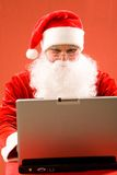 Santa and laptop Stock Images