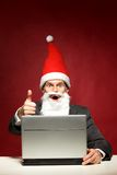 Santa with laptop. Showing thumbs up Stock Photos