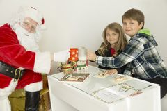 Santa Claus with kids at the table. Santa on the left side of the image and boy and girl on the right side of this horizontal image. they are have a cups in Royalty Free Stock Photo