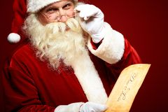 Santa with letter. Portrait of happy Santa Claus holding Christmas letter in his hands and looking at camera Royalty Free Stock Photos