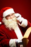 Santa with letter. Portrait of happy Santa Claus holding Christmas letter in his hands and looking at camera Royalty Free Stock Photography