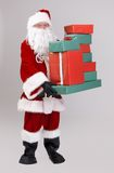 Santa lifting christmas presents. Full size portrait of Santa lifting christmas presents, looking at camera, isolated on gray background royalty free stock image