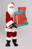 Santa lifting christmas presents Royalty Free Stock Image