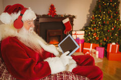 Santa listening music and touching tablet Stock Photos