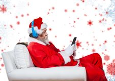 Santa listening to headphones and using digital tablet while sitting on a couch Stock Image