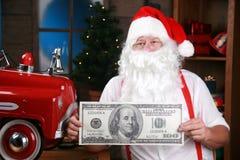 Santa lleva a cabo cientos cuentas de dólar gigante Foto de archivo