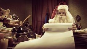 Santa with a long Christmas list. Santa Claus reading a very long Christmas list and looking at camera Royalty Free Stock Photo
