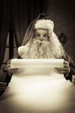 Santa with a long Christmas list Stock Images