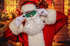 Santa in luminous glasses. DJ Santa Claus in luminous glasses and headphones holds a party near his house decorated with lights. Christmas songs and music stock photo