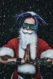 Santa in luminous glasses. Portrait of a cool punk Santa Claus in luminous glasses with bright dreadlocks over black background stock photography