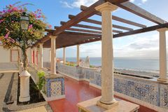 Santa Luzia viewpoint miradouro with columns and tiles in the foreground and Santa Estevao Church and Tagus river in the backgro Royalty Free Stock Photo