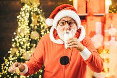 Santa make funny face and picking cookie. Santa Claus takes a cookie on Christmas Eve as a thank you gift for leaving