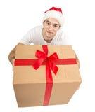 Santa man looking up, holding gift.  Royalty Free Stock Image