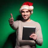 Santa man making  ok  gesture while reading on tablet Stock Photography