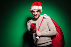 Santa man is offering you a small gift box Royalty Free Stock Photo