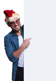 Santa man is presenting a blank board. Young santa man is presenting a blank board by pointing finger to it Stock Images