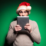 Santa man is shocked while reading on tablet Royalty Free Stock Photography