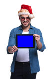Santa man showing the blank screen of a tablet. Young man wearing santa hat is showing the blank screen of a tablet pad computer Royalty Free Stock Photo
