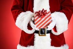 Santa: Mani in pieno dei regali di Natale Fotografia Stock