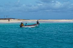 4 fishermen boating along a coastline. Island Sal, Cape Verde. Santa Maria, Cape Verde - May 04, 2016: 4 fishermen boating along a coastline stock photos