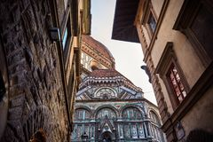 Santa Maria del Fiore. The Cattedrale di Santa Maria del Fiore shows its majesty peeking between two old buildings in the beautiful city of Firenze, Italy Royalty Free Stock Images