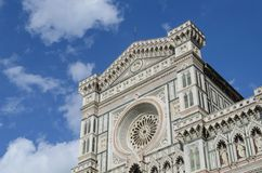 Santa Maria del Fiore rose window in clear sky, Florence. View of the top of the facade and the rose window of the cathedral of Florence, Santa Maria del Fiore Royalty Free Stock Image