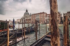Santa Maria della Salute, Grand Canal view with gondolas around a wooden pier in a rainy autumn day, Venice, Italy Royalty Free Stock Photos