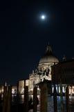 Santa Maria della Salute i Venedig på natten med den över huvudet månen Arkivbild