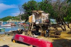 SANTA MARTA, COLÔMBIA - 10 DE OUTUBRO DE 2017: Vista exterior de muitos barcos na água e em um barco cor-de-rosa na areia na Imagens de Stock