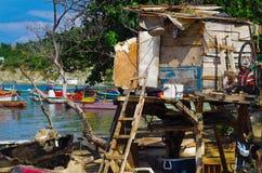 SANTA MARTA, COLÔMBIA - 10 DE OUTUBRO DE 2017: Vista exterior de muitos barcos na água e de uma cabana de madeira velha em um car Foto de Stock Royalty Free