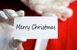 Santa Merry Christmas. Santa Claus holding a white card with a written Merry Christmas message Royalty Free Stock Images