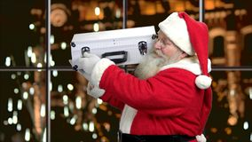 Santa with metal case of money. Businessman in costume of Santa Claus is opening silver case on evening city background. Financial and business theme stock video