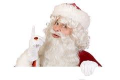 Santa mettant le doigt vers le haut Photographie stock libre de droits