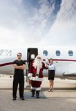Santa with modern sleigh. Santa exiting his modern sleigh with body guard Royalty Free Stock Photography