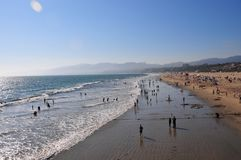 Santa Monica Beach in California. Busy day at Santa Monica Beach. View of the water with people walking, swimming and playing. Family fun. Sand, waves, sunlight Stock Image