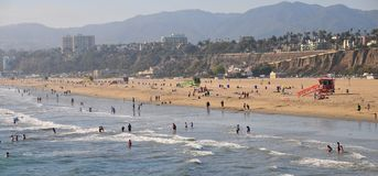 Santa Monica Beach in California. Busy day at Santa Monica Beach. View of the water with people walking, swimming and playing. Family fun. Sand, waves, sunlight Royalty Free Stock Images