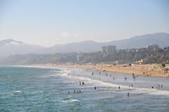 Santa Monica Beach in California. Busy day at Santa Monica Beach. View of the water with people walking, swimming and playing. Family fun. Sand, waves, sunlight Stock Images