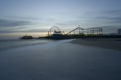 Santa Monica Beach with Pier. Horizontal image of the Pacific Wheel at the Santa Monica Pier amusement park.   Long exposure with misty looking waves during Royalty Free Stock Photo