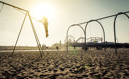 Santa monica beach. silhouette of a woman going up with the swing stock images