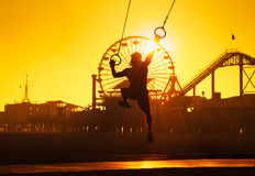 Santa Monica Beach sunset. Silhouette of a man in a baseball cap swinging on rings near the Pier on the beach at Santa Monica, California stock photo