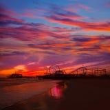 Santa Monica California sunset on Pier Ferrys wheel. And reflection on beach wet sand Royalty Free Stock Photos