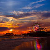 Santa Monica California sunset on Pier Ferrys wheel. And reflection on beach wet sand Royalty Free Stock Images