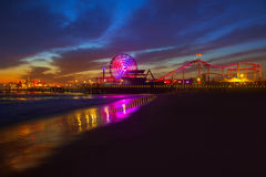 Santa Monica California sunset on Pier Ferrys wheel. And reflection on beach wet sand Royalty Free Stock Image