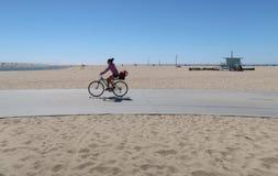 Santa Monica Kalifornien, USA 03 31 bikepath 2017 på stranden med cyklisten och den typiska livräddaren står högt i bakgrund Fotografering för Bildbyråer