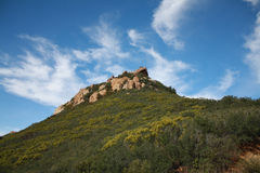 Blue Sky Behind Rocky Hill. The volcanic rocks of Santa Monica Mountain that can be seen along the Backbone trail toward Sandstone Peak. A sea of different wild Royalty Free Stock Images