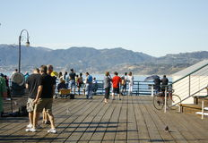 Santa Monica Pier. Santa Monica, CA November 13, 2010 crowd of visitors and tourists looking at the mountains and Pacific Ocean Royalty Free Stock Photo